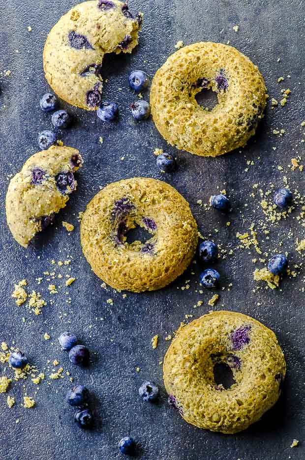 Bird's eye view of three lemon blueberry cake donuts stacked on a black surface with some fresh blueberries scattered around