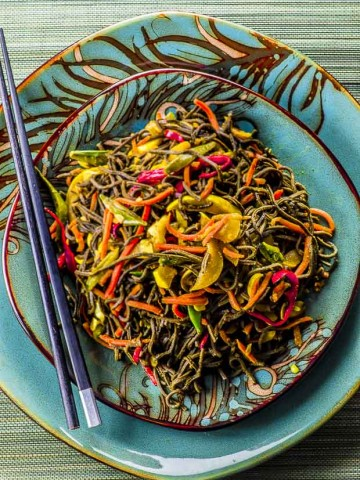 A green plate full of High protein Singapore noodles, placed on top of a larger green plate.