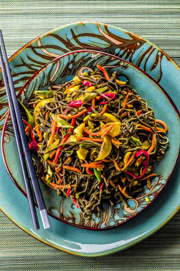 Birds eye view of high protein Singapore noodles, on a teal plate, placed on top of a larger matching plate.