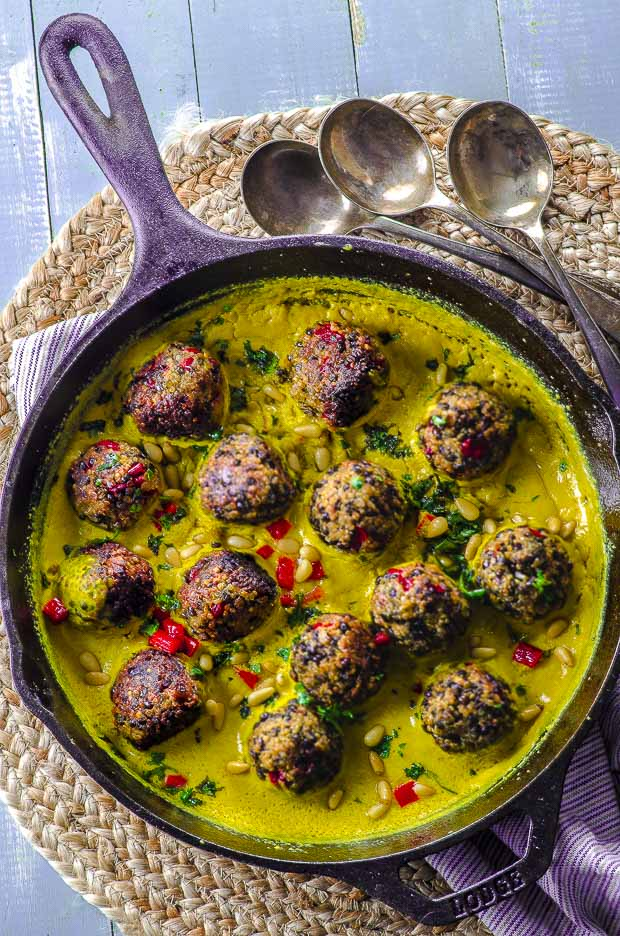 bird's-eye view of a cast iron skillet with Quinoa lentil meatballs with tahini turmeric sauce