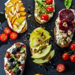 Bird's eye view of 5 crostini topped with ricotta cheese and various toppings