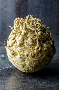 A celeriac ( celery root) in a black background