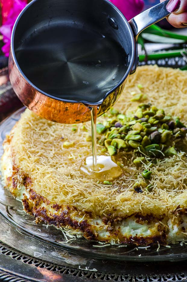 A Knafeh pie with pistachios on top with orange blossom syrup being poured on top