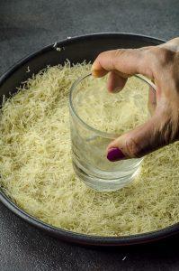 pressing kataifi at the bottom of a cake pan