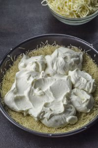 ricotta on top of kataifi in a round pan