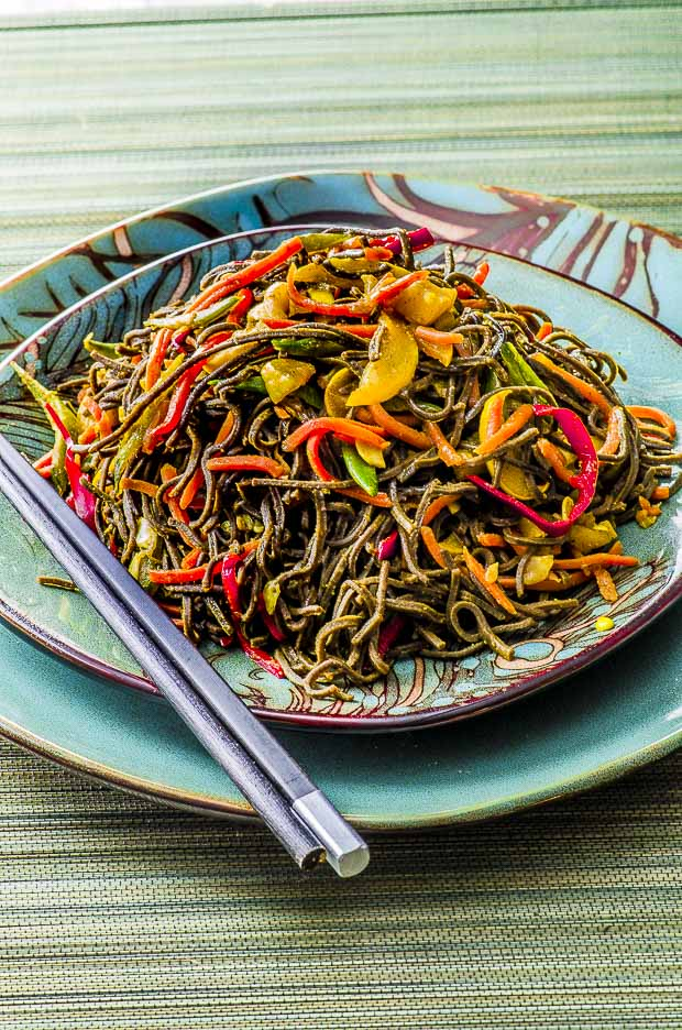 Close up of high protein Singapore noodles, on a teal plate, placed on top of a larger matching plate, with chopsticks on the side
