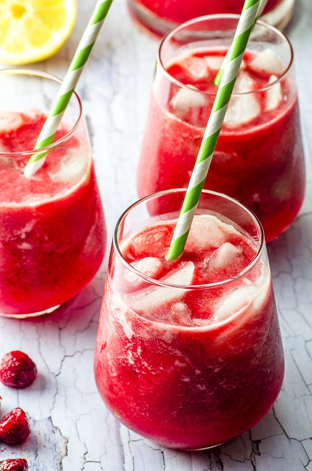 three glasses filled with date sweetened raspberry lemonade with green and white paper straws
