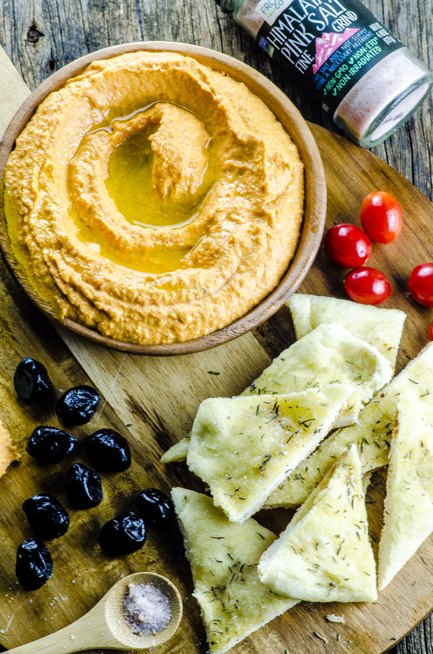 Birds eye view of harissa hummus on a wooden board with flat bread triangles, olives and grape tomatoes scattered