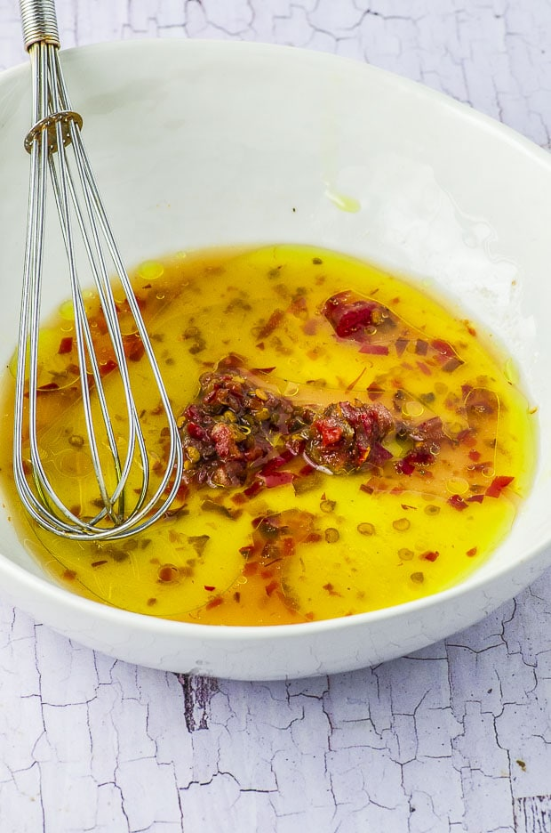 Close up of the salad dressing in a bowl, with a metal whisk