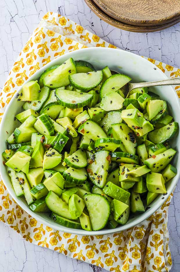 Birds eye view of the avocado cucumber salad in a white bowl, over a white and yellow cloth napkin
