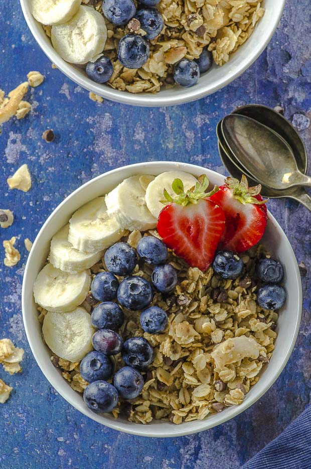 bird's eye view of two bowls of coconut nut-free granola with strawberries and blueberries