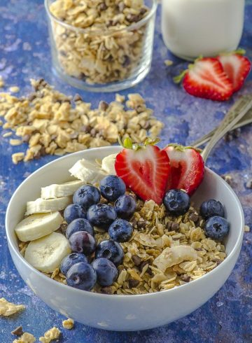 A bowl of nut free coconut granola with strawberries and blueberries