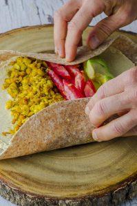 rolling a breakfast burrito