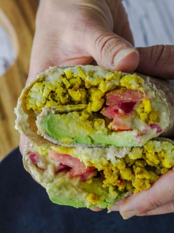 hands holding a tempeh breakfast burrito with tomato and avocado
