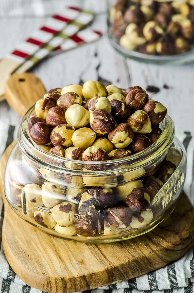 Close up of roasted hazelnuts in a small glass jar on a wooden cutting board
