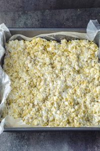 Close up of the melted marshmallows and crispy rice mixture pressed into the baking dish