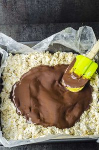 Close up of the melted chocolate being spread on top of the rice crispy treats