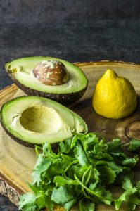 Clse up of an avocado sliced in half, fresh cilantro and haf a lemon on a wooden board