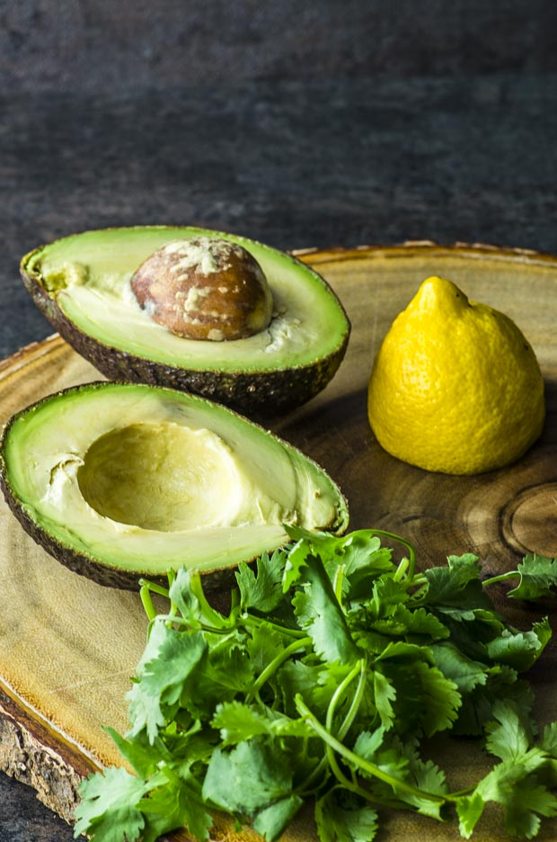 Avocado, cilantro and fresh lemon in a wood cutting board ready for the green dressing