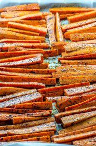 Close up of raw seasoned carrots on a baking sheet
