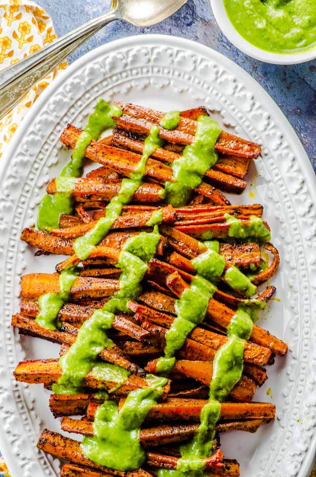 Birds eye view of Chili Roasted Carrots with Avocado Cilantro Dressing in a white oval platter