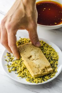 Dipping tofu in nutritional yeast and sesame seeds for a veggie sandwich