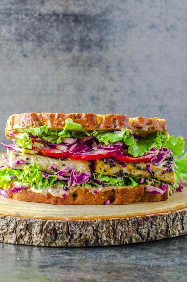 Asian inspired tofu Veggie sandwich on around wood surface
