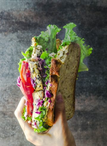 A hand holding an asian inspired tofu veggie sandwich