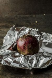 A beet ready to be wrapped in aluminum foil
