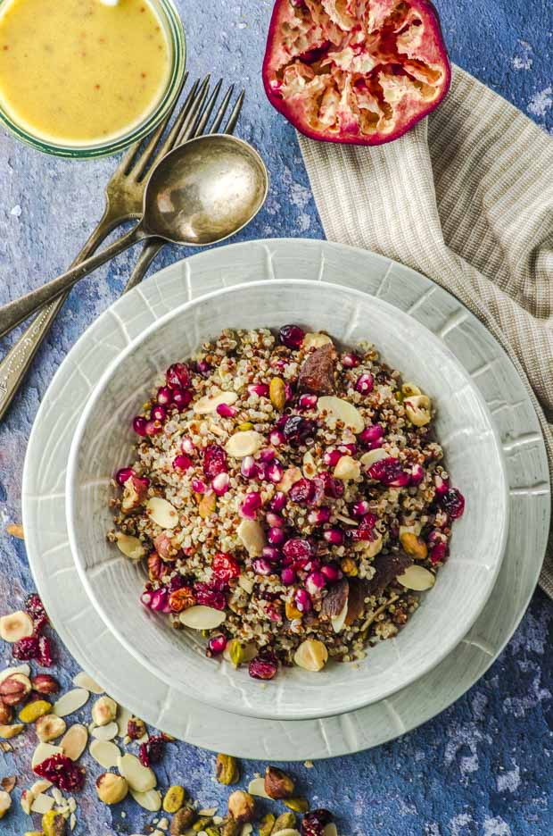 Bird's eye view of a plate filled with a quinoa salad topped with pomegranates and nuts