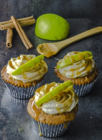 Three Apple caramel vegan cupcakes on a black surface