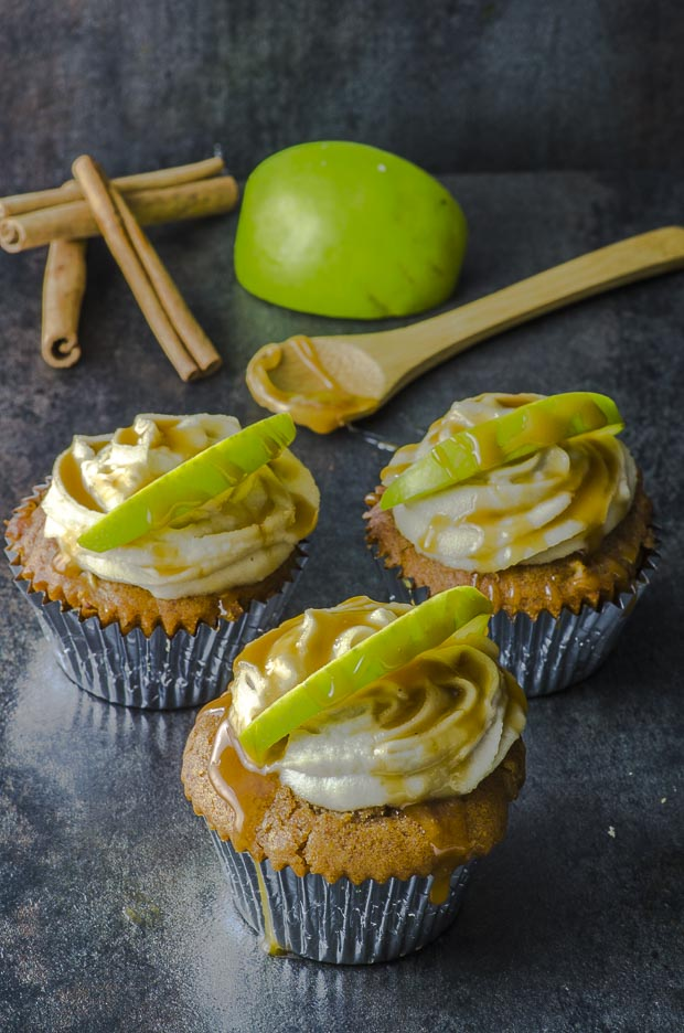 Three sea salt caramel apple vegan cupcakes on a black surface