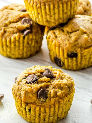 close up of a pumpkin muffing with other pumpkin muffins on the back