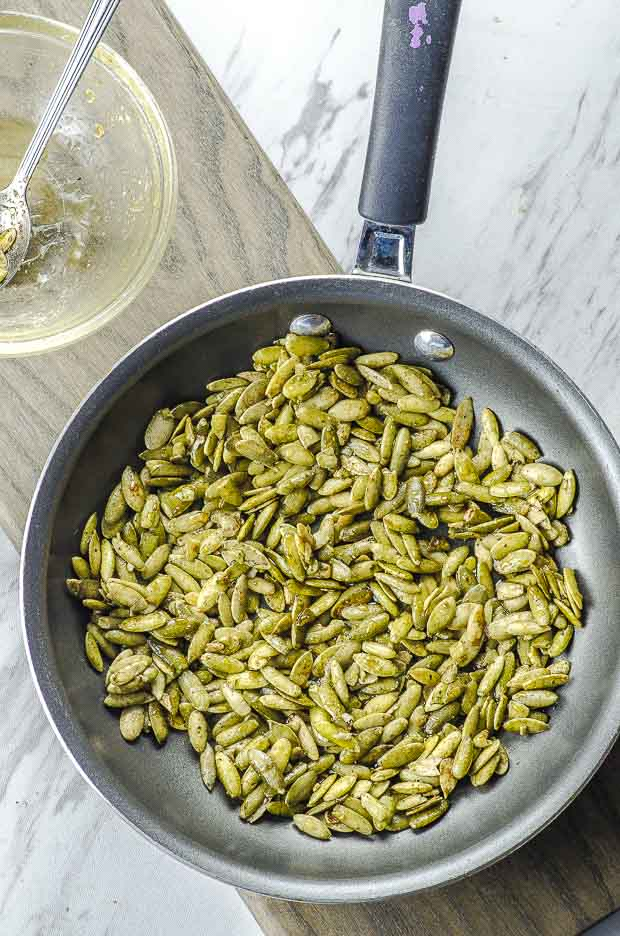 cinnamon ginger spiced pumpkin seeds in a pan ready to cook