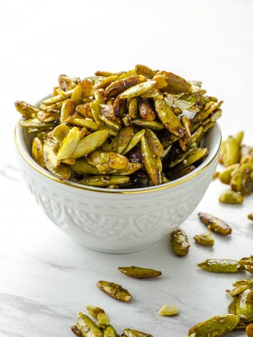 a white bowl filled with cinnamon ginger spiced pumpkin seeds