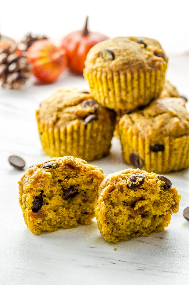 One chocolate chip pumpkin muffin cut in half and three pumpkin muffins piled on the back of the image