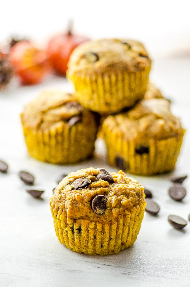 One chocolate chip pumpkin muffin and three pumpkin muffins piled on the back