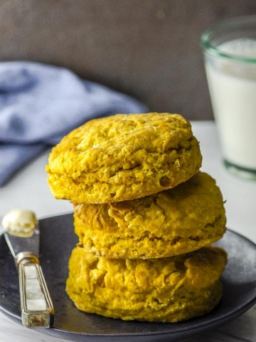 Three sweet potato biscuits stacked on a black plate
