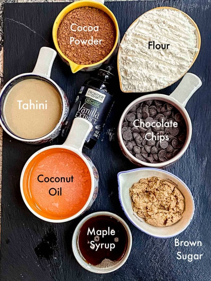 Labeled ingredients to make double chocolate chip cookies. flour, brown sugar, cocoa poder chocolate chips, vanilla extract, tahini, maple syrup and coconut oil