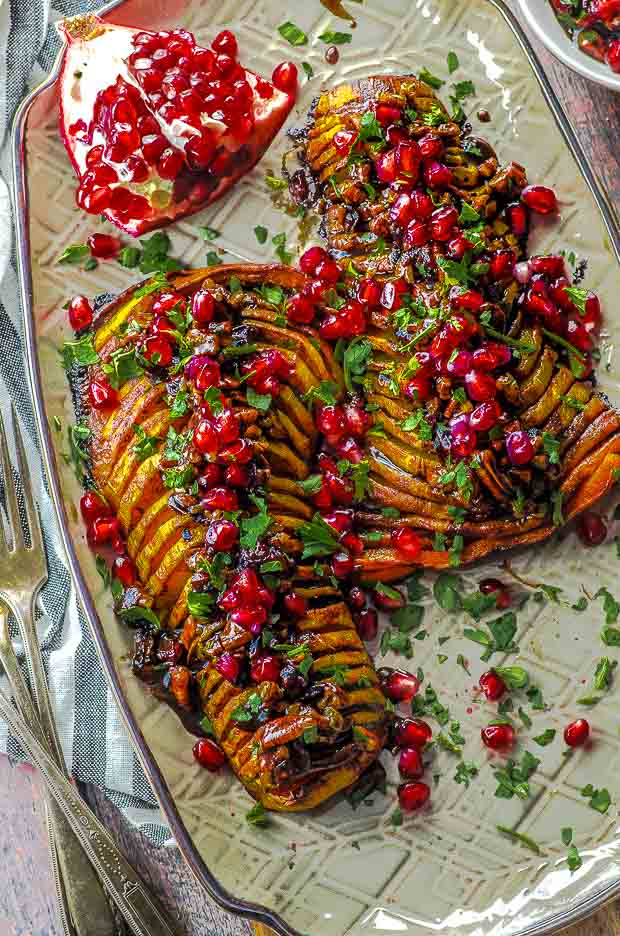 Close up bird's eye view of two hasselback butternut squash topped with cranberries, pecans and pomegranates