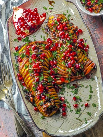 Birds eye view of two hasselback butternut squash topped with cranberries, pecans and pomegranates