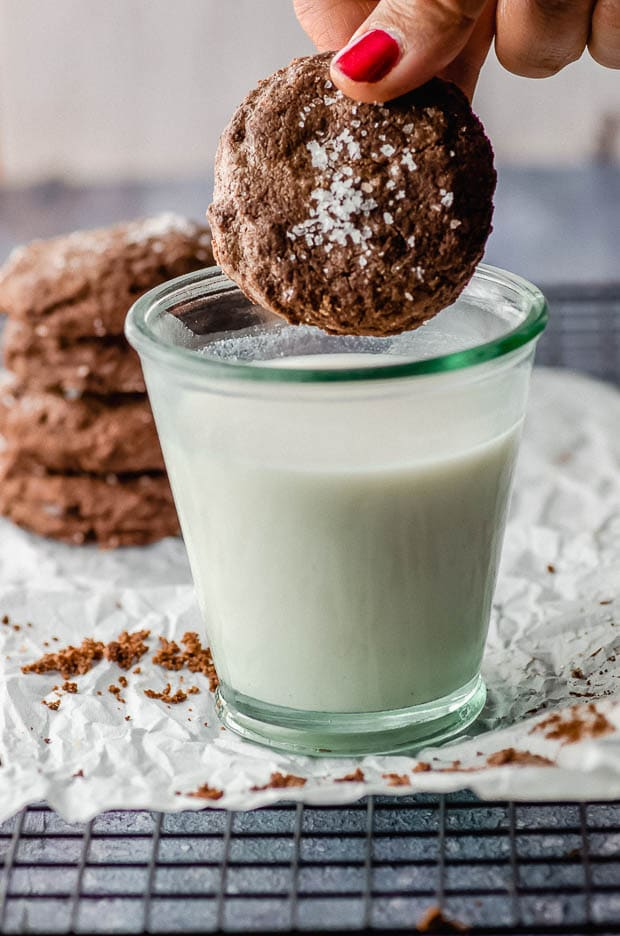 A double chocolate chip cookies dipped in a glass of milk