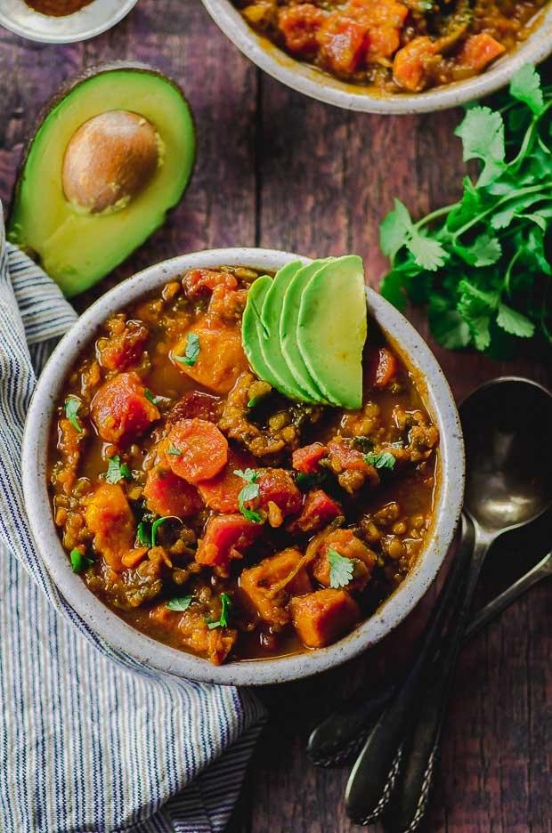 A bowl of sweet potato lentil vegan chili topped with avocado