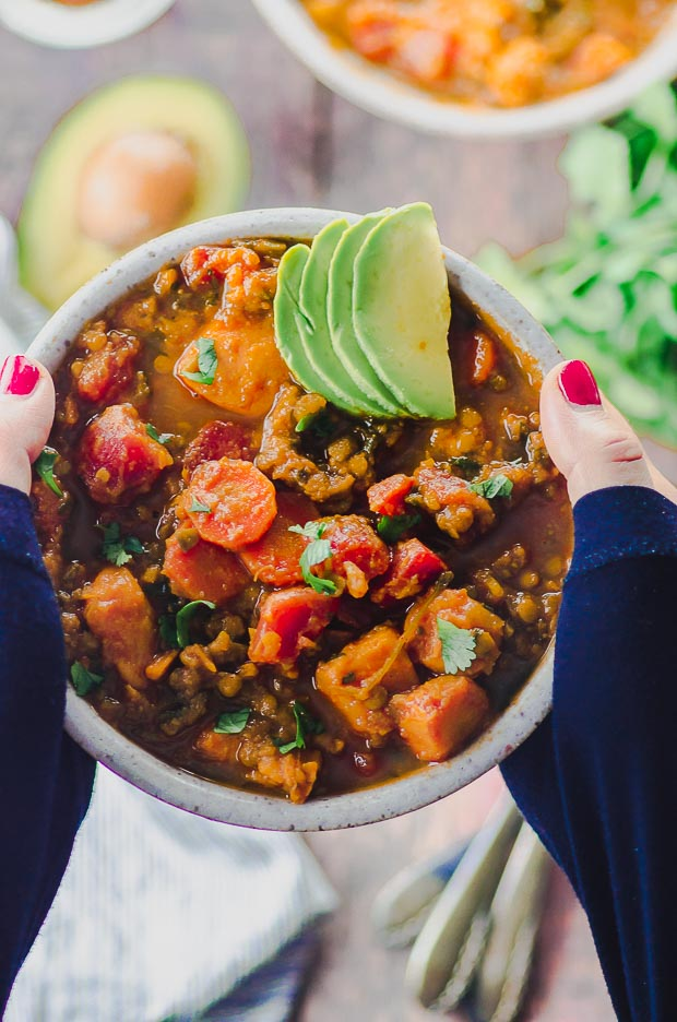 two hands holding a A bowl of sweet potato lentil vegan chili topped with avocado