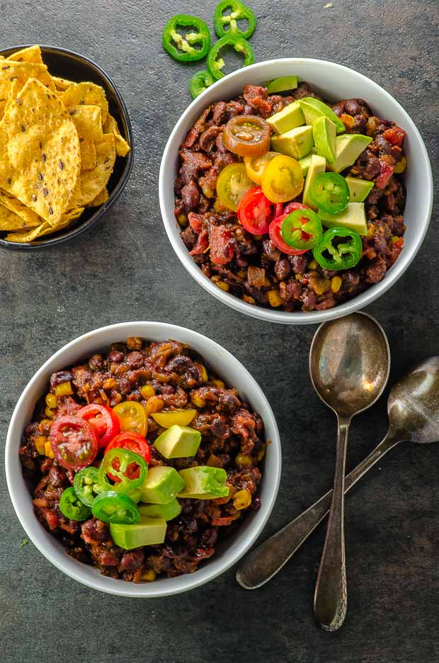 Bird's eye view of two plates of black bean chili
