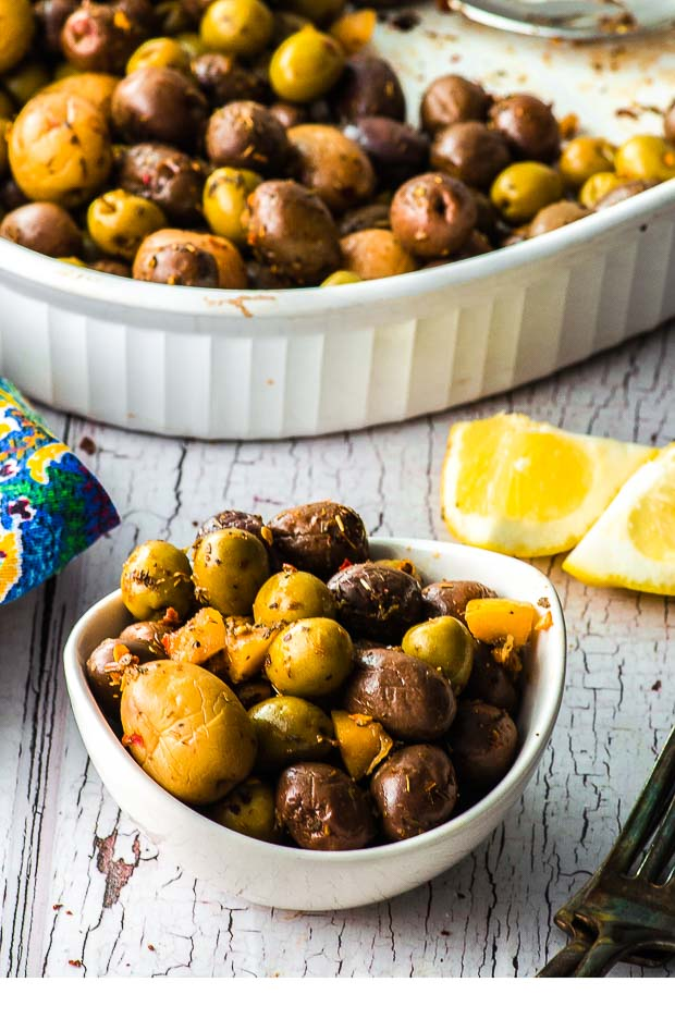 Side View of a small bowl with roasted olives and a large baking dish on the background with more roasted olives