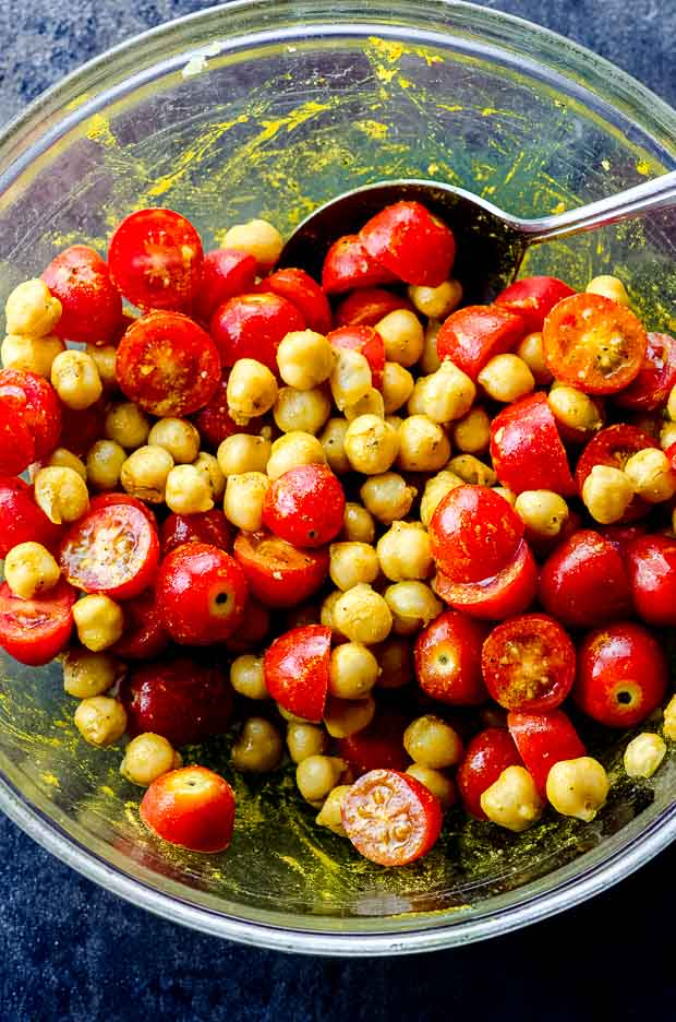 A bowl with chickpeas spices and cut tomatoes for chickpea salad