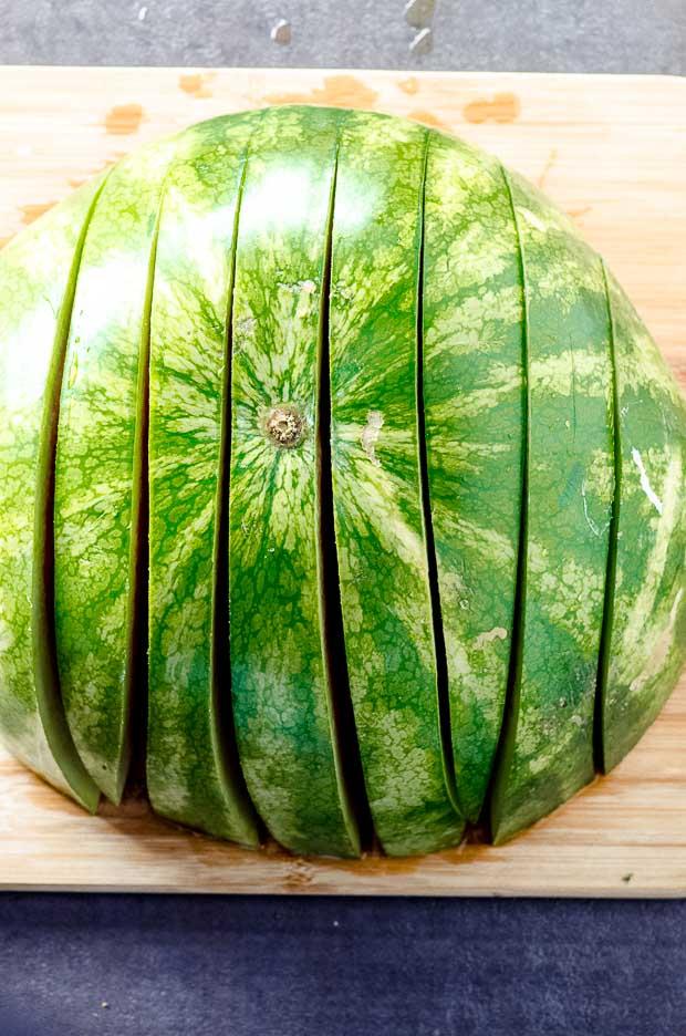 Half a sliced watermelon on a cutting board