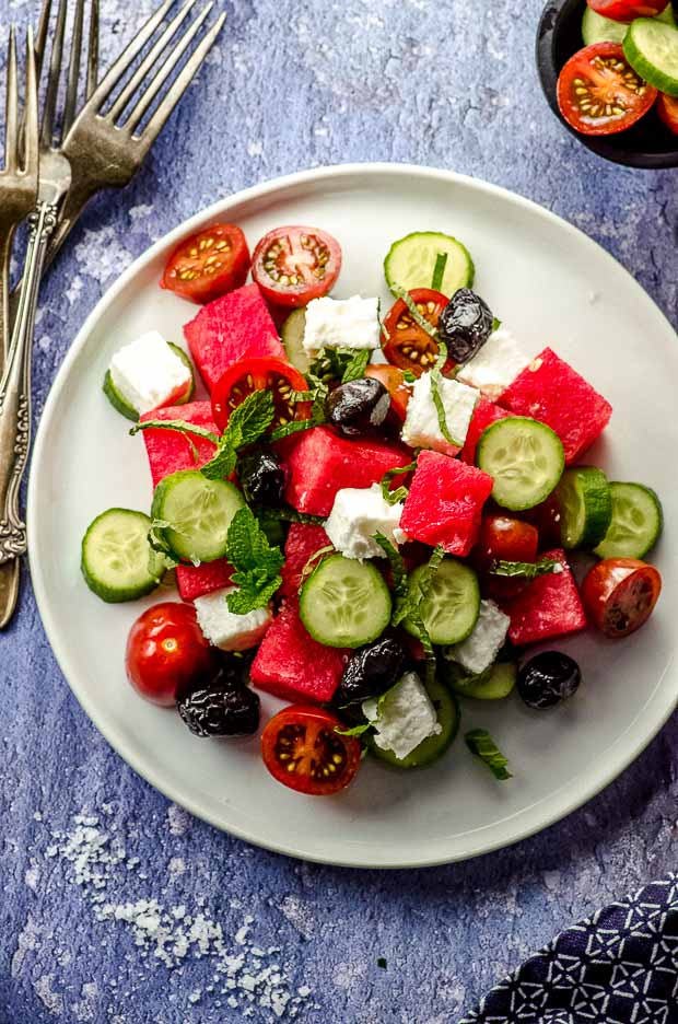 Bird's eye view of a white plate with cucumber feta watermelon salad