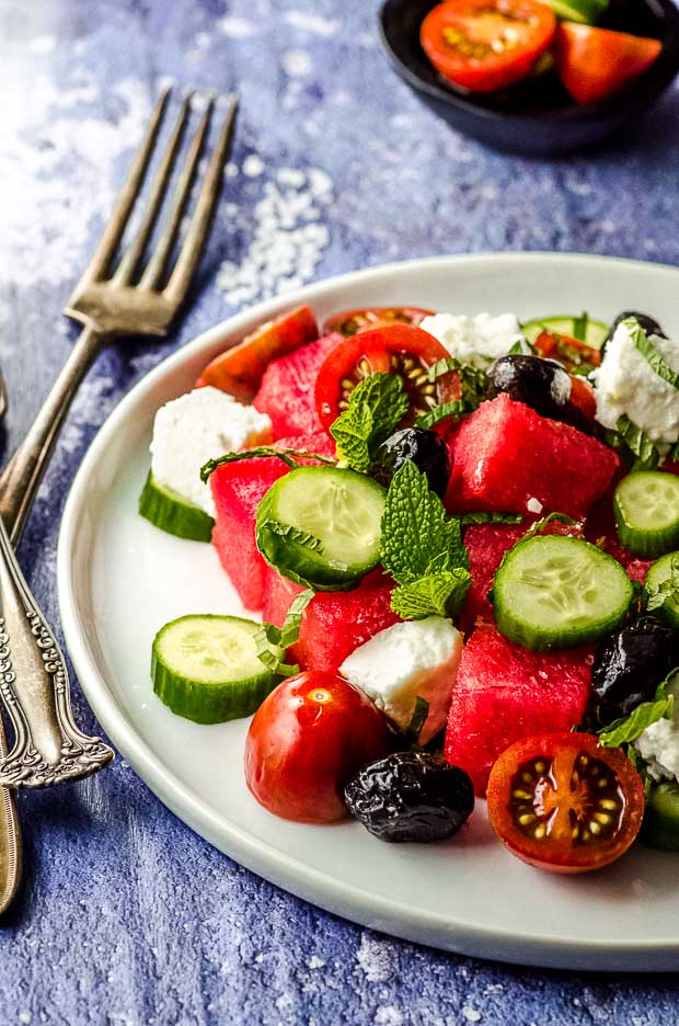Side view of a cucumber, feta, tomato, watermelon salad